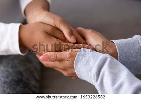 African american adult woman foster care parent single black mother holding hands of child teen daughter give support love protection, charity and adoption, family trust help concept, close up view #1653226582