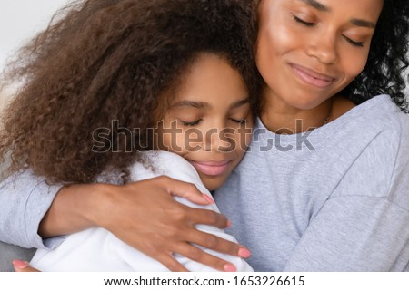 Caring african american single mother hugging teenage daughter, happy black mom embracing teen girl cuddling enjoy moment of love, mum and child warm relationship, motherhood concept, close up view #1653226615