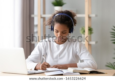 Focused african american teenage girl wearing headphones writing notes study with laptop and books, serious black female high school teen student listening audio course or music while doing homework Royalty-Free Stock Photo #1653226624