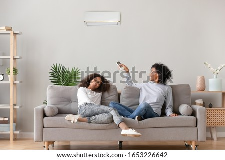 Happy african family relax on sofa under air conditioner, black mom holding remote control switch on conditioning in living room adjust comfort temperature for daughter, climate system at modern home #1653226642