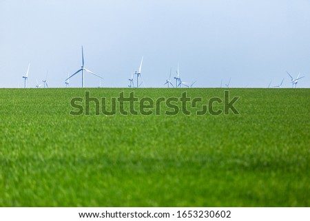 Alternative wind energy. Wind turbines generating electricity on sunny field #1653230602