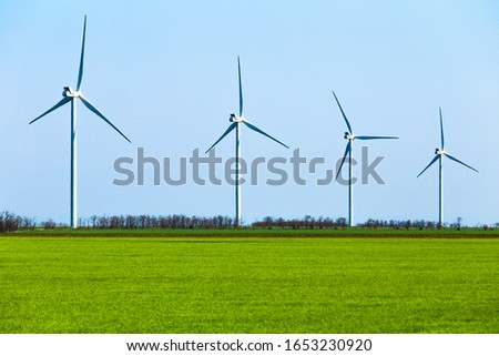 Huge wind turbines and bright colors of the meadow. Power of nature concept #1653230920