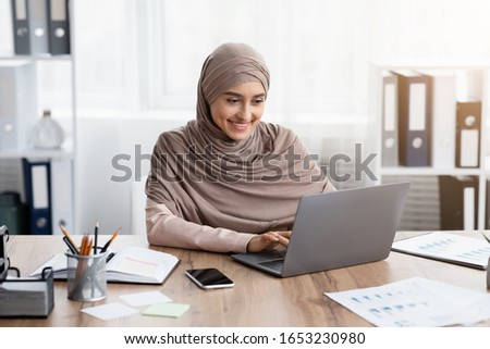 Young muslim businesswoman working on her laptop in office, typing on keyboard while sitting at desk in modern workspace #1653230980