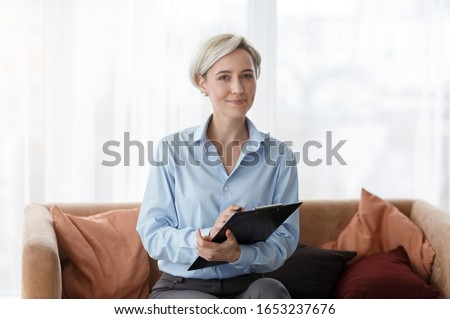Professional Psychotherapy. Successful Psychologist Holding Folder Smiling To Camera Sitting On Sofa In Office. Royalty-Free Stock Photo #1653237676
