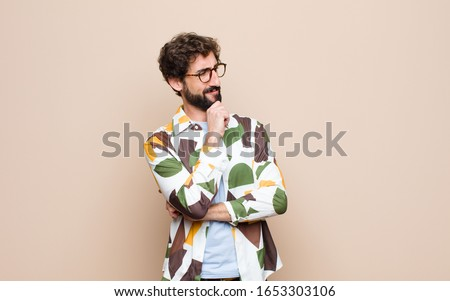 young cool bearded man expressing a concept against flat wall #1653303106