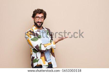 young cool bearded man expressing a concept against flat wall #1653303118