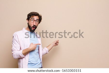 young cool bearded man expressing a concept against flat wall #1653303151