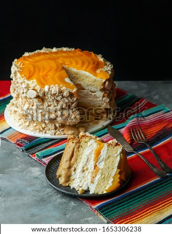 Uruguayan cake chaja: the famous sponge cake from Uruguay,  sponge cake stuffed with syrup, dulce de leche, whipped cream and peaches.                             #1653306238