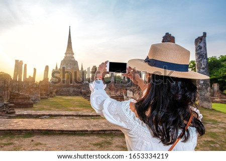 Tourist woman taking a picture with a mobile phone in touristic ruins of Ayutthaya in Thailand #1653334219