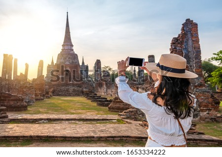 Tourist woman taking a picture with a mobile phone in touristic ruins of Ayutthaya in Thailand #1653334222