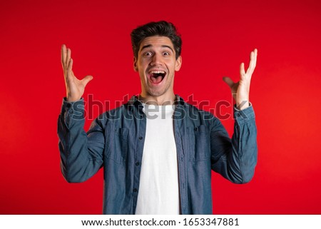 Man in blue shirt very glad and happy, wow effect, he smiling, screaming. Surprised excited happy guy on red studio background #1653347881