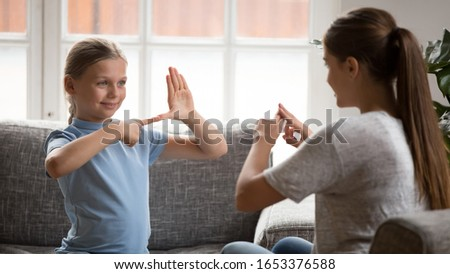 Smiling happy adorable girl sitting on couch, making hands sign, practicing learning language, communicating nonverbal with deaf dumb young mother. Hearing loss disability person lifestyle concept. #1653376588
