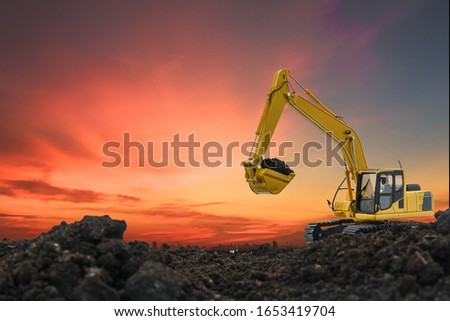 Excavators are digging the soil in the construction site on the orange  sky background #1653419704