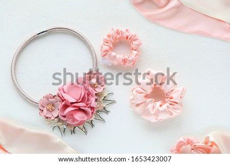 Pink hair accessories with roses. silk Pink Scrunchy isolated on white backdrop. Flat lay Hairdressing tools and accessories as Color Hair Scrunchies, Elastic HairBands, Bobble Scrunchy Hairband