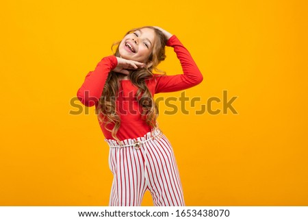 charming european girl in a red blouse and striped pants smiles on a yellow background #1653438070