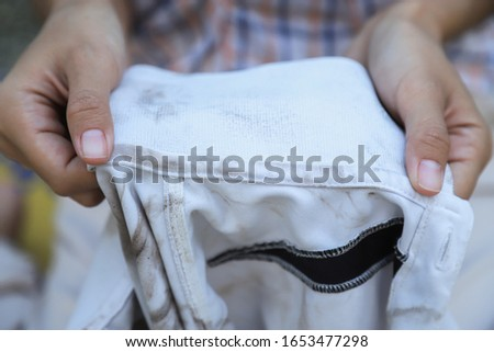 hand hold dirty stain on shirt at collar in house. people with dirt stains in daily life for cleaning concept  #1653477298
