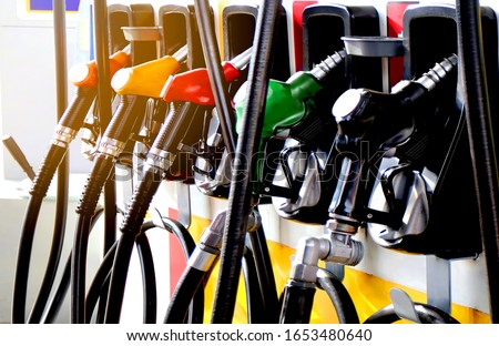 colorul fuel gasoline dispenser with sun flare background  Royalty-Free Stock Photo #1653480640