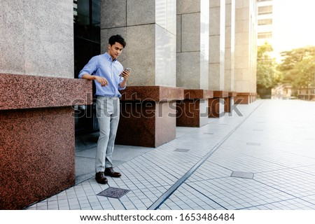 Happy Young Businessman in Casual wear Using Mobile Phone in the City. Lifestyle of Modern People. Full Length #1653486484