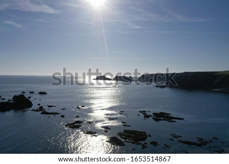 rocker shoreline with sun reflecting during summer #1653514867