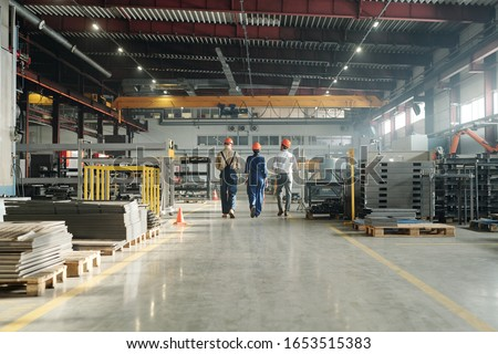 Rear view of three technicians or engineers of industrial plant in workwear leaving workshop at the end of working day Royalty-Free Stock Photo #1653515383