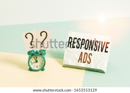 Writing note showing Responsive Ads. Business photo showcasing Automatically adjust form and format to fit existing ad space Alarm clock beside a Paper sheet placed on pastel backdrop. #1653553129