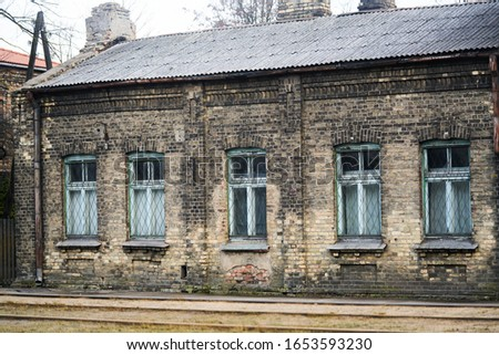 Aged weathered street wall with some windows Royalty-Free Stock Photo #1653593230