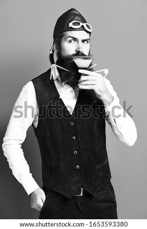 handsome bearded pilot or aviator man with long beard and mustache on serious face holding glass of alcoholic beverage in vintage suede leather waistcoat with hat,. and glasses on red studio #1653593380