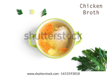 Chicken and vegetables broth or soup isolated on white background, top view, copy space. Homemade healthy meal - cooking fresh chicken or turkey soup.