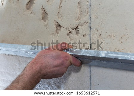 Construction worker with a long spatula to plaster the wall by hand. #1653612571