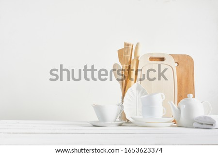 Kitchen background for mockup with spoon, teapot, cups, rolling pin, bowls on wooden table on white background. Blank space for home kitchen concept. #1653623374
