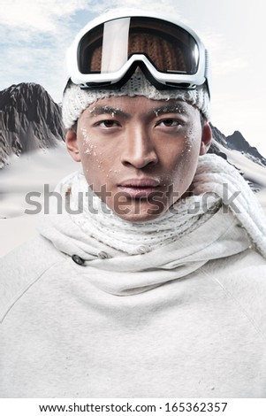 Asian winter holiday fashion man in arctic snow landscape. Wearing woolen hat, sweater, scarf and ski glasses. #165362357