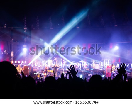 crowd at concert - summer music festival in front of bright stage lights. Dark background, smoke, concert spotlights.people dancing and having fun in summer festival party outdoor #1653638944