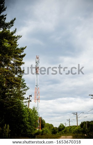 Mobile phone communication antenna tower with sky and clouds.New 5G radio network telecommunication equipment with radio modules and smart antennas mounted on a metal tower radiating strong signal #1653670318
