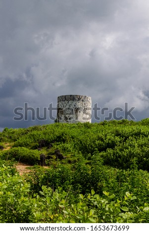 Old tower on a green hill with dark clouds in the background #1653673699