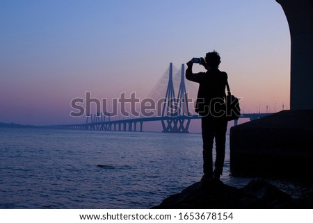 A photographer clicking picture of bandra worli sea link. Silhouette of a person clicking picture of rajiv gandhi sea link by standing on a rock in Mumbai, India.