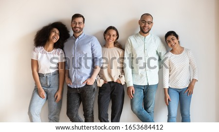 Attractive jovial multi-ethnic friends girls guys leaned on grey beige wall pose smiling looking at camera feels happy. Concept of racial equality and friendship, millennial generation people portrait #1653684412