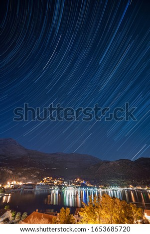 Landscape of a night town on beachfront with star trails on a deep blue sky, long exposure #1653685720