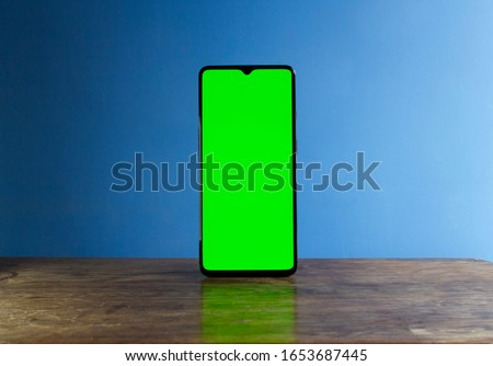 A smart phone on its own, stood up in portrait orientation. It has a blank, green screen display, for mock-ups like showing app development, or to use in a graphic design. Cell phone is isolated.