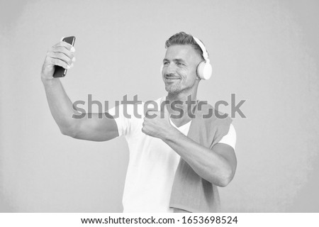 Selfie in gym concept. Healthy lifestyle. Gym aesthetics. Mature but still in good shape. Exercising in gym for better health. Man athlete taking selfie photo. Sportsman smartphone and headphones.