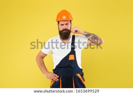 Improvement and renovation. Brutal man builder. Engineer builder in uniform. Man builder hard hat. Handyman at workshop. Creativity and practice. Polished approach. Craftsman keep head safe in helmet. #1653699529