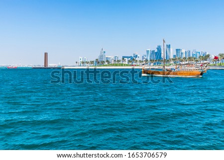 Doha, Qatar February 12, 2020: Old wooden boats dhows with Qatari flags in Doha Harbor and City Skyline in Distance #1653706579