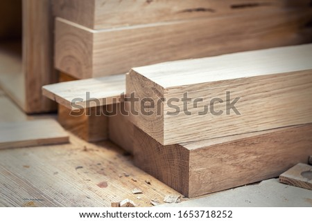 Oak wooden bar blocks materials stacked at carpentry woodwork workshop with tools and sawdust on background. Timber wood blanks at diy workbench. Close-up lumber beam details. Handcraft hobby #1653718252