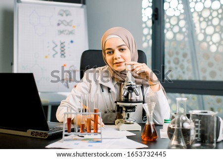 Pretty female muslim scientist doctor lab technician pharmacist working in the laboratory with microscope, test tubes with blood samples, using laptop and writing notes during experiment #1653732445