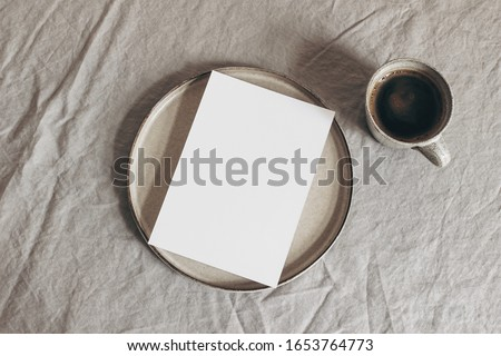 Cup of coffee and blank greeting card, invitation on ceramic plate. Moody breakfast table mockup scene. Beige linen tablecloth background. Sparse still life composition  Rustic flat lay, top view. #1653764773