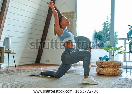 Young beautiful athletic girl in leggings and top makes lunges. Healthy lifestyle. Woman doing exercises at home. #1653772798