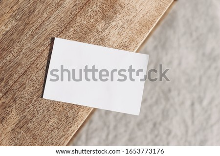 Closeup of blank business card on teak wooden table. Blurred beige linen background. Empty paper card mockup scene in neutral colors. Branding, business concept. Sparse composition Top view.