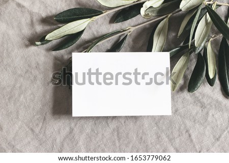 Closeup of blank greeting, business card and green olive leaves, branches on  linen tablecloth background.  Moody feminine wedding stationery mock-up scene. Flat lay, top view. Mediterranean design
