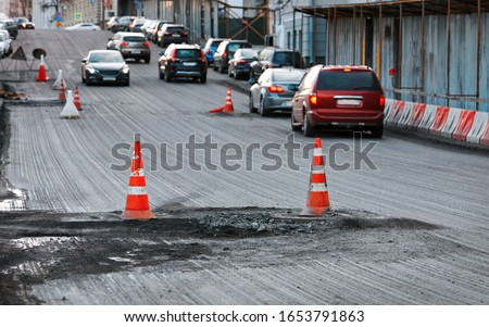 Road works and construction, traffic cone. Pylon with white and orange stripes on asphalt. Traffic signs for signaling. Road maintenance, under construction sign and traffic cones on damaged road