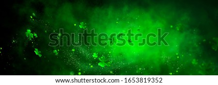 St. Patrick's Day abstract green background decorated with shamrock leaves. Patrick Day pub party celebrating. Abstract Border art design magic backdrop. Widescreen clovers on black with copy space. Royalty-Free Stock Photo #1653819352