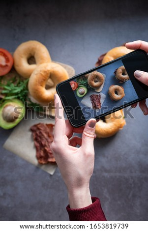 Woman taking a picture of breakfast with a mobile phone. Salmon bagel and bacon bage on concrete background. Vertical picture. Blogging concept